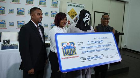Ganhador de loteria recebe prêmio com máscara para não ser identificado